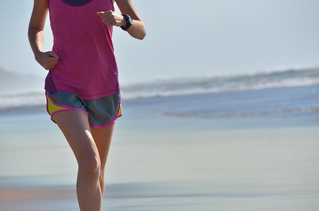 Mujer con hábitos saludables corriendo en la playa