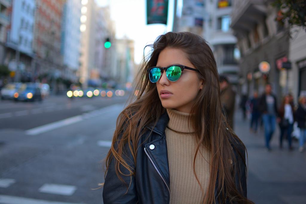 Chica joven con gafas de sol en la ciudad